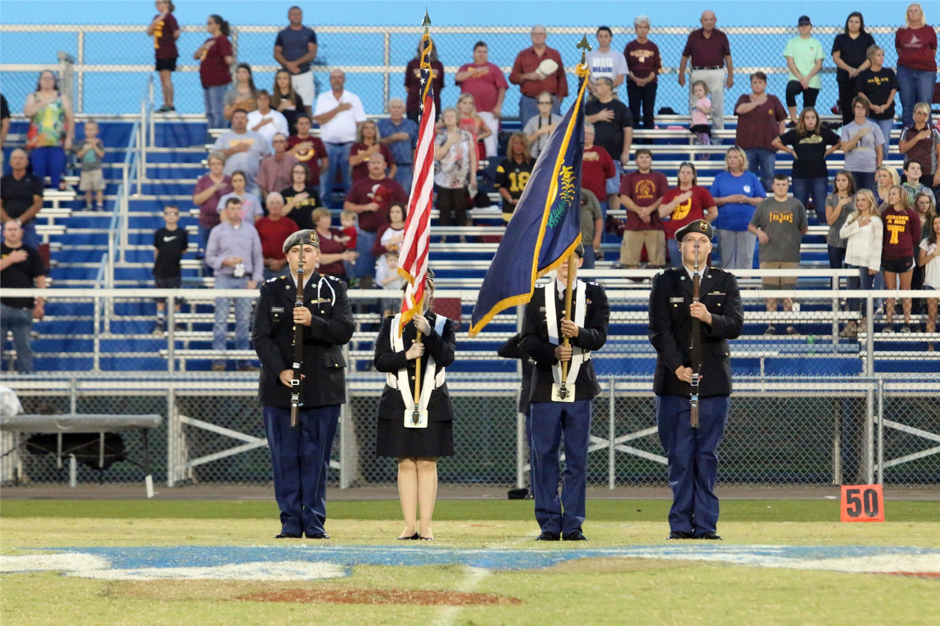 JROTC Cadets presenting flag at football game.