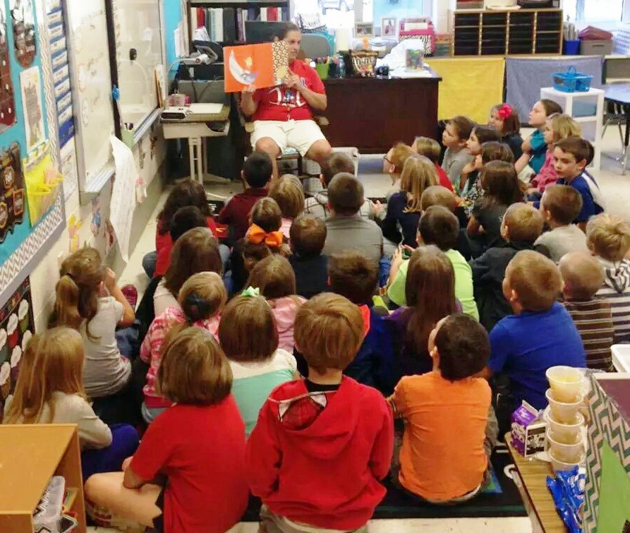 Primary students listen as a Food Service Worker reads a story.
