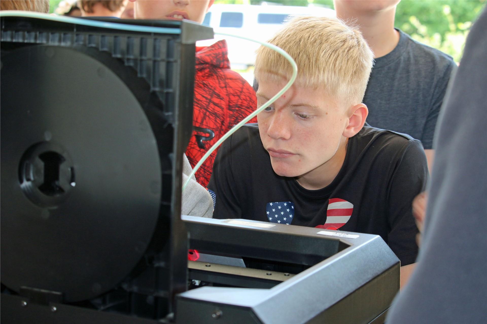 ACIC student studies 3-D printer.